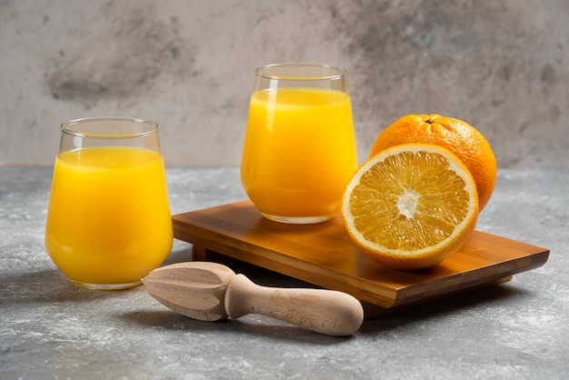 Стеклянные стаканы с апельсиновым соком и деревянная развертка. Бесплатные Фотографии