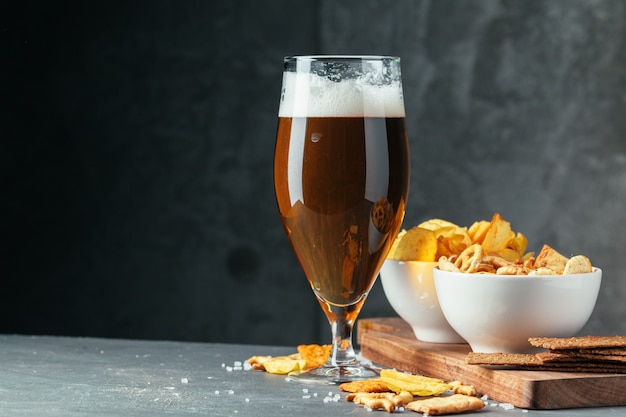 Glass of dark beer with bowl of beer snacks close up Premium Photo