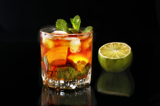 Glass of dark rum cocktail with lime, orange, ice cubes and mint leaves on black mirror background. Premium Photo