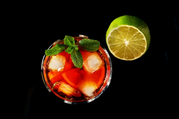 Glass of dark rum cocktail with lime, orange, ice cubes and mint leaves . Premium Photo