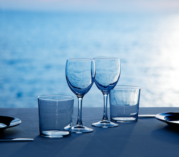 Glass dish cups and glasses on blue sea Premium Photo