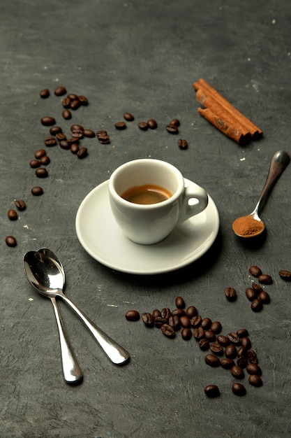 Glass of espresso coffee in grey background decorated with coffee beans Free Photo