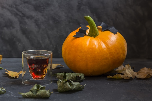 Ð␠glass in the form of a skull and fall halloween pumpkins on a dark background. Premium Photo