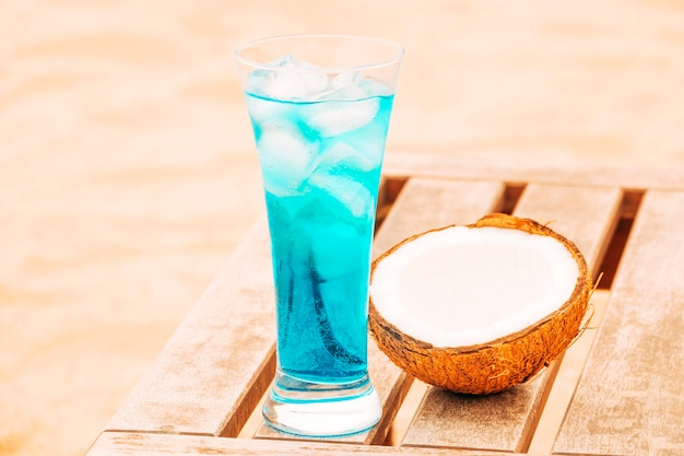 Glass of fresh blue drink and cracked coconut at wooden table Free Photo