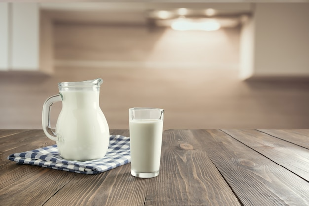 Glass of fresh milk and jug on wooden tabletop with blur kitchen as background. Premium Photo