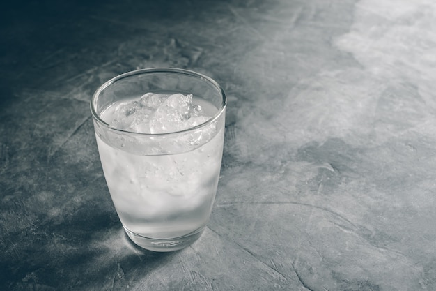 Glass of fresh mineral water with ice cubes on cement table with vintage color. empty ready for your product display or montage. Premium Photo