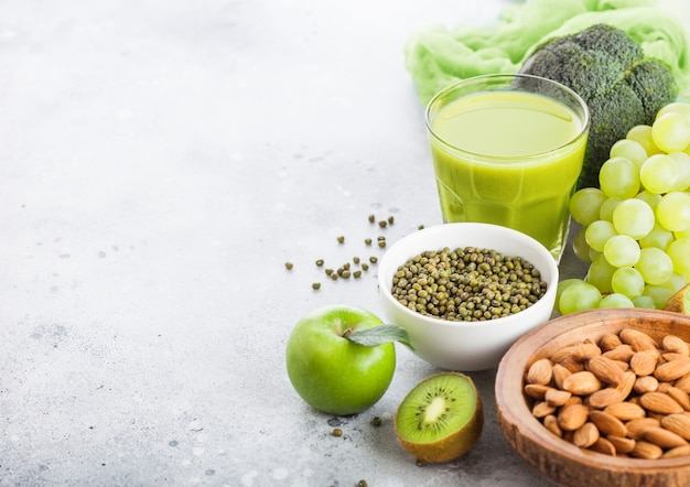 Glass of fresh smoothie juice organic green toned fruit and vegetables on stone kitchen. with almond and mung beans nuts in bowl. Premium Photo