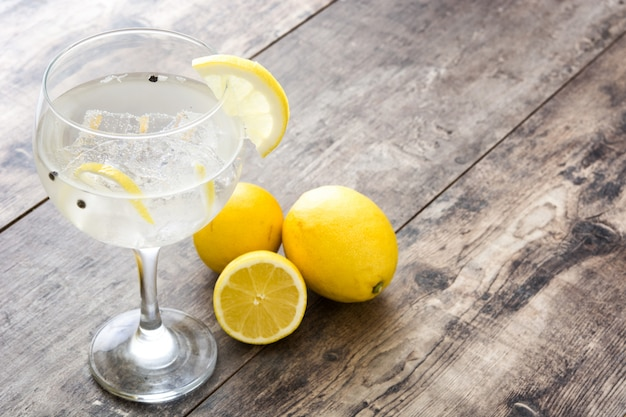 Glass of gin tonic with lemon on wooden table Premium Photo