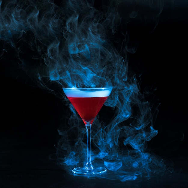 Glass goblet with red smoky liquid Free Photo