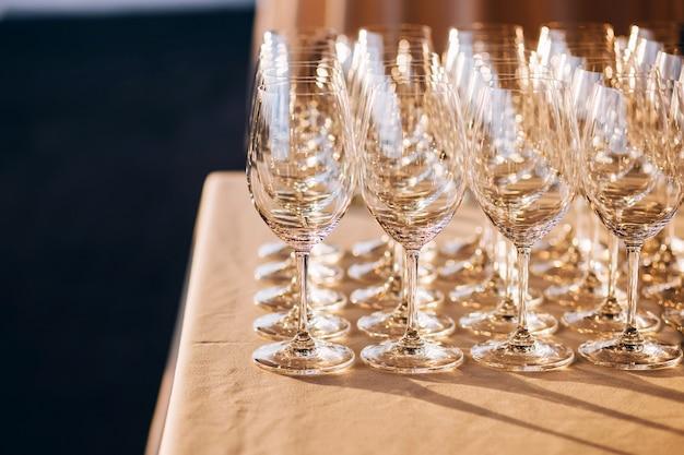 白いテーブルの上のガラスのゴブレット。空のクリスタルワイングラス。高い脚にガラスの杯。白いテーブルクロスに多くの空のグラス Premium写真