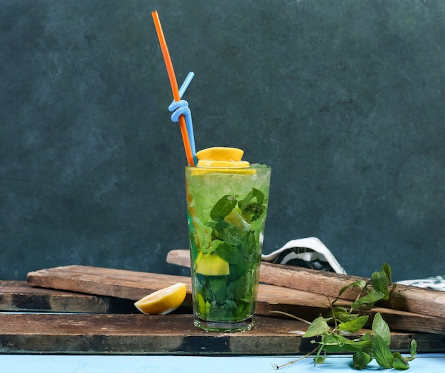 A glass of green mojito with lemon on a piece of wood. Free Photo