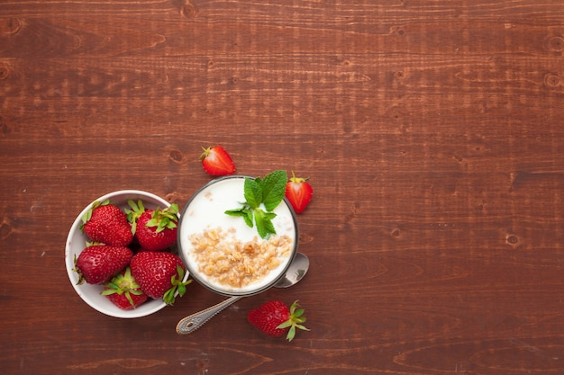 Glass of healthy strawberry yogurt with fresh berries on wooden table top view Premium Photo