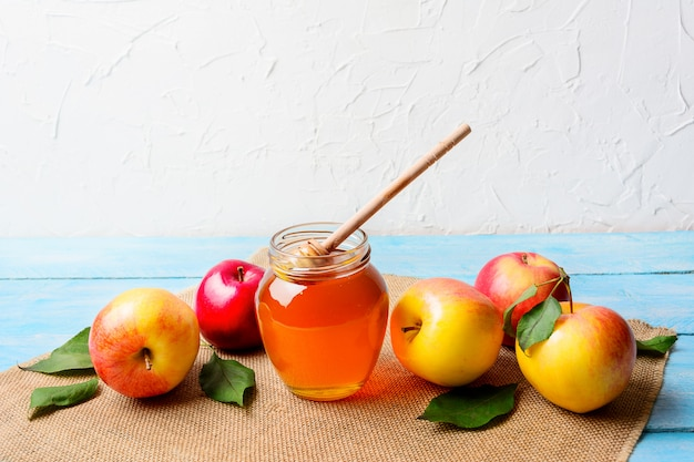 Glass honey jar with dipper and apples copy space Premium Photo