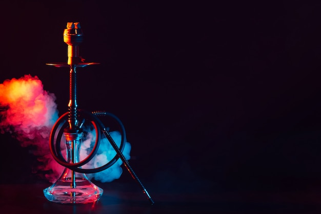 Glass hookah shisha with a metal bowl on the table on a black background with smoke and colored neon lighting Premium Photo