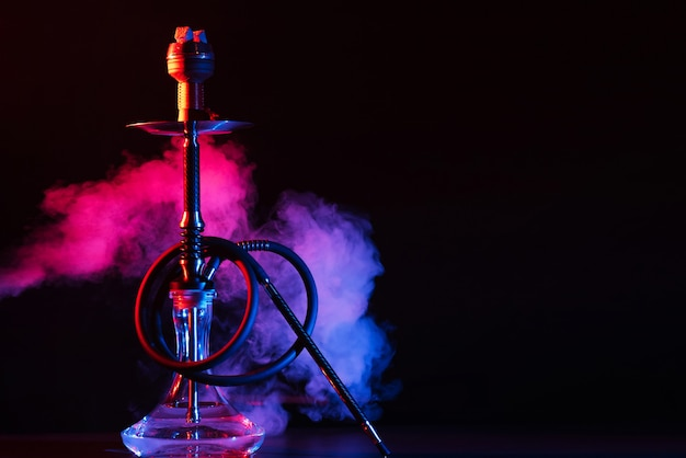 Glass hookah shisha with a metal bowl on the table Premium Photo