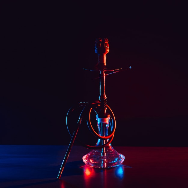 Glass hookah with a metal bowl with hot coals on a black background on a table in a restaurant Premium Photo