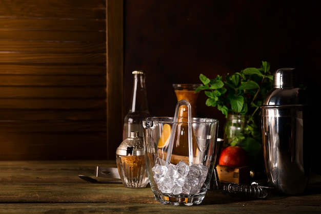 Glass ice bucket and different cocktails in glass with bar accessories isolated on black Premium Photo