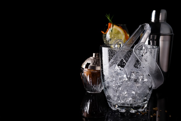 Glass ice bucket and mohito cocktail in glass isolated on black Premium Photo