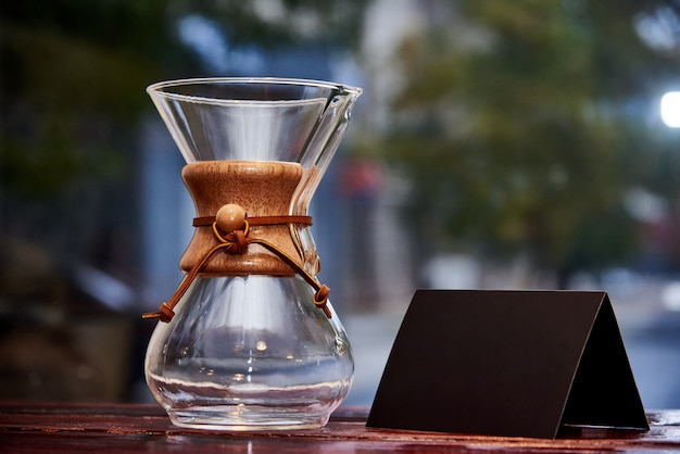 Glass jar and black card on a wooden surface. Premium Photo
