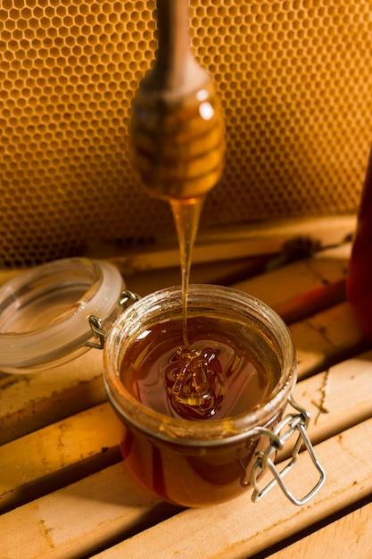 Glass jar full of honey with honey spoon Free Photo