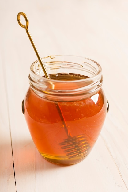 Glass jar full of honey with honey spoon Free Photo