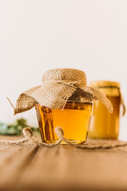 Glass jar full of honey on wooden table Free Photo