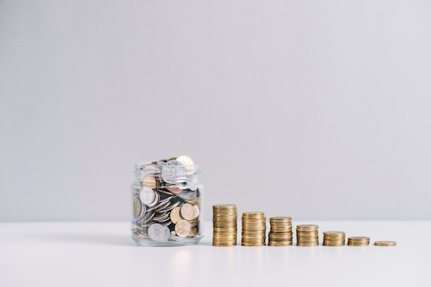 Glass jar full of money in front of decreasing stacked coins against white background Free Photo