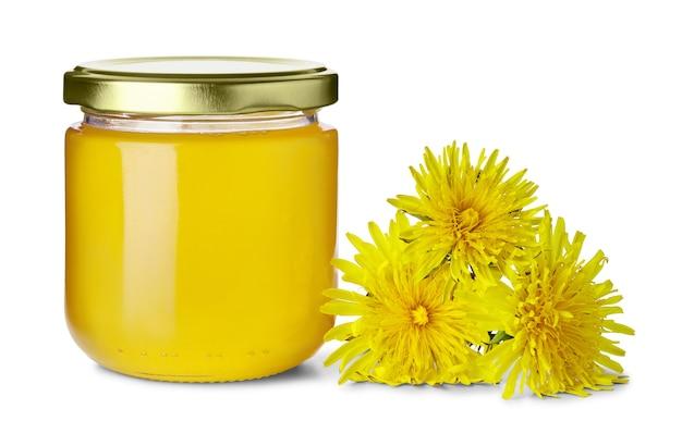 Стеклянная банка, полная сладкого цветочного меда и цветов одуванчика рядом с изолированным на белом фоне Premium Фотографии