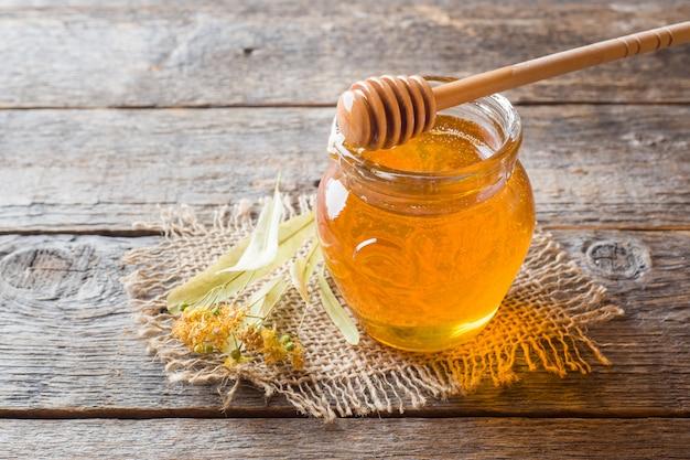 Glass jar of honey, linden flowers on wooden surface Premium Photo