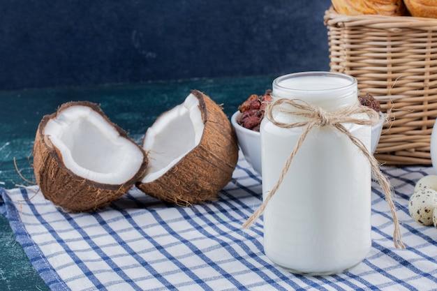 大理石のテーブルに牛乳とハーフカットココナッツのガラス瓶。 無料写真