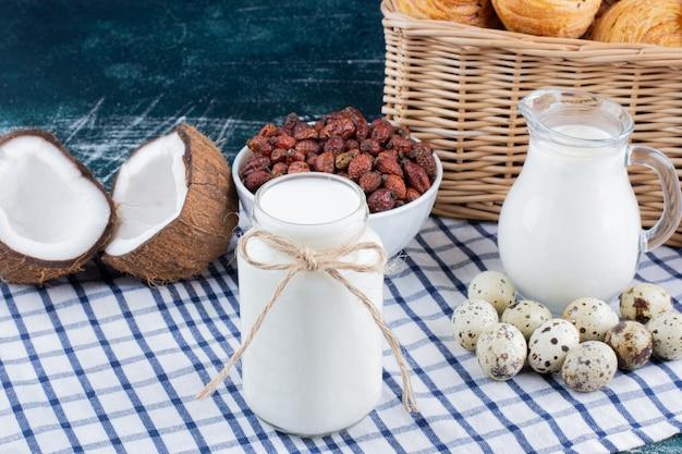 大理石のテーブルに牛乳、乾燥ナツメヤシ、ウズラの卵のガラス瓶。 無料写真