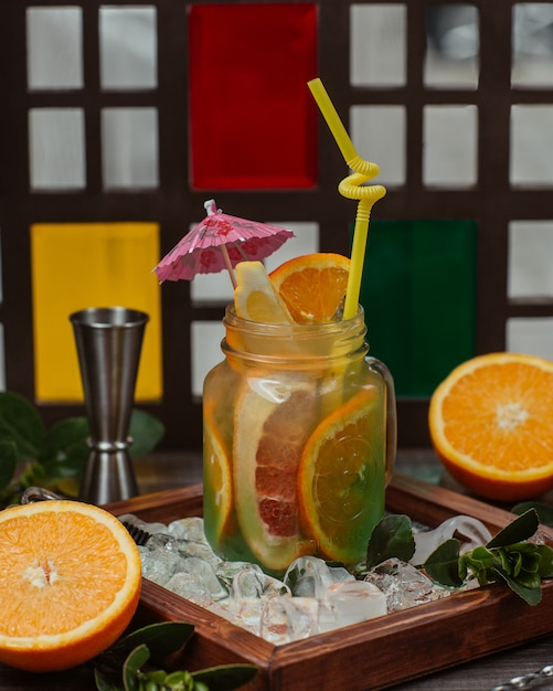 A glass jar of orange, lemon and grapefruit cocktail with fruit slices. Free Photo