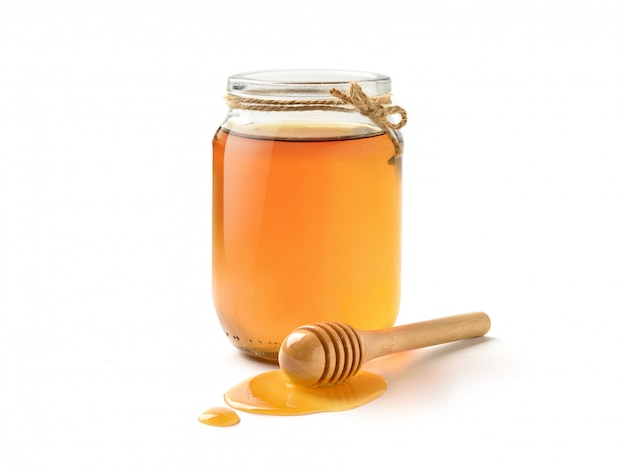 Glass jar of pure honey with honey dipper isolated on white background. Premium Photo