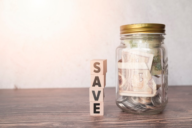 Glass jar for savings with wooden word Free Photo