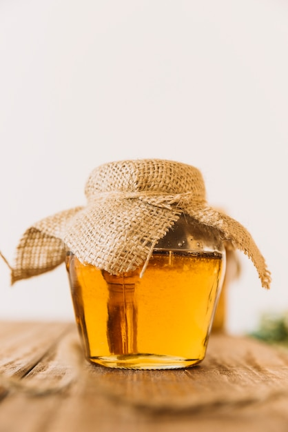 Glass jar of sweet honey on wooden table Free Photo