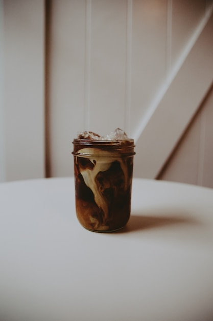 Glass jar with coffee glasse with cream in it on a white table Free Photo