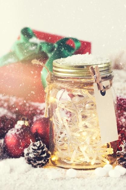 Glass jar with lights and christmas decorations with snow for Christmas glass jar decorations