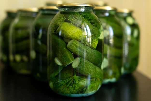 Glass jar with pickled cucumbers on gray Premium Photo