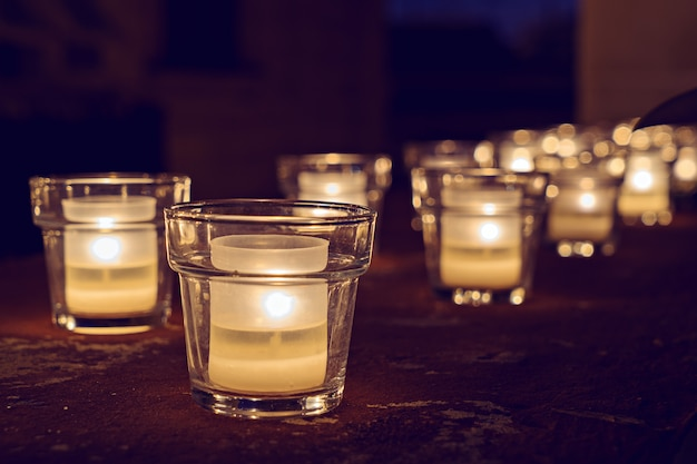 Glass jars with burning candles on the dark Premium Photo