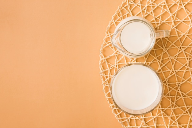 Glass and jug of milk on the coaster over the colored background Free Photo