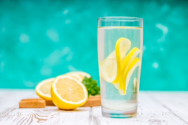 A glass jug with a cold lemonade on a white wooden background surrounded by lemons. Premium Photo