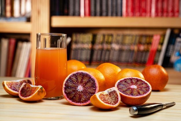 Glass of juice, knife and cut red oranges on a light wooden table Premium Photo