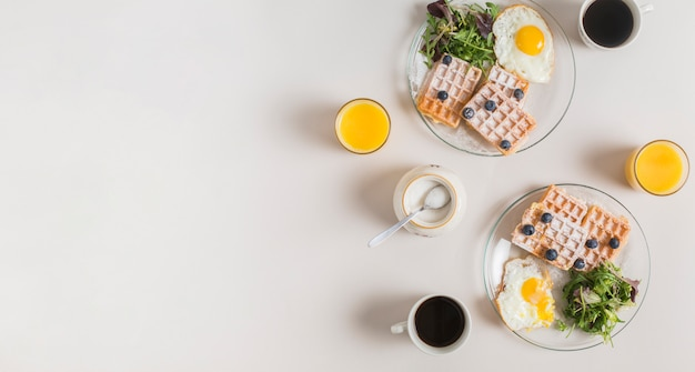 Glass of juice; powdered milk; tea and healthy salad with waffle and fried eggs on plate over white backdrop Free Photo