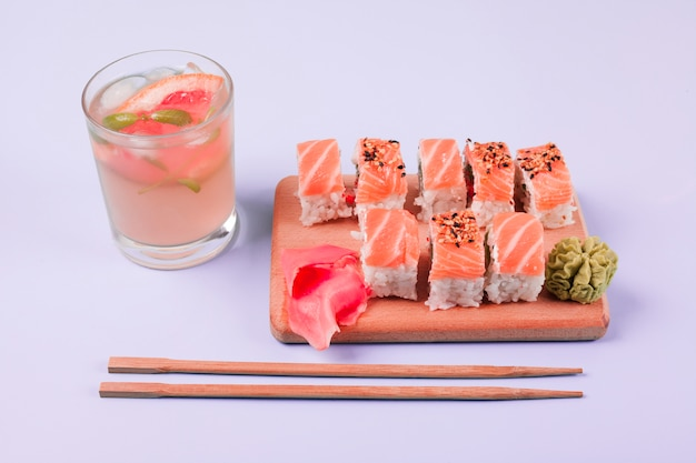 A glass of juice with classic salmon sushi; wasabi and pickled ginger on chopping board with chopsticks against white backdrop Free Photo