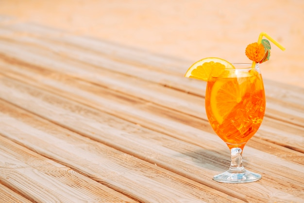 Glass of juicy orange drink on wooden table Free Photo