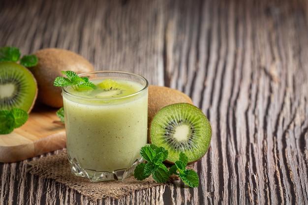 Bicchiere di succo di kiwi messo sul pavimento di legno Foto Gratuite