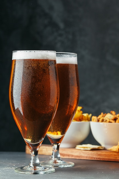 Glass of lager beer with snack bowls Premium Photo