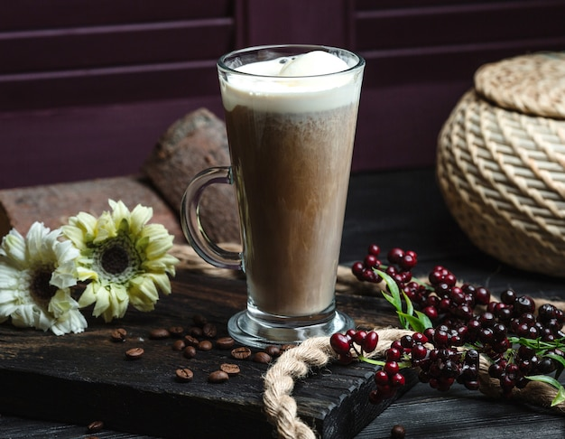 Glass of latte with foam decorated with coffee beans and flowers Free Photo