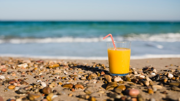 A glass of mango juice with drinking straw on sand at beach Free Photo