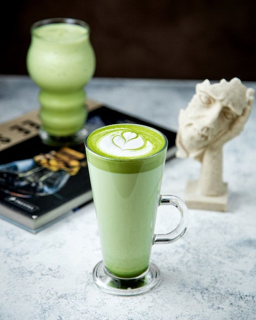 A glass of matcha green tea with latte art on top 1 Free Photo